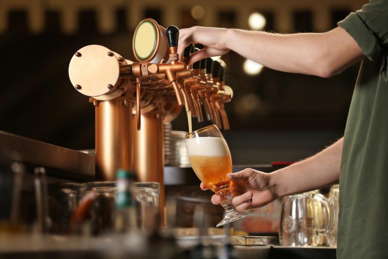 Бармен наливает пиво в бокал фото