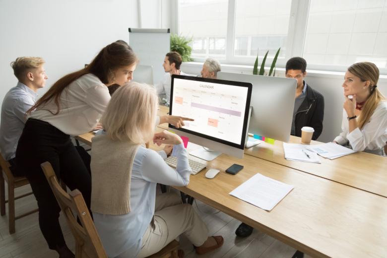 Менеджер помогает сотрудникам осваивать новое программное обеспечение фото