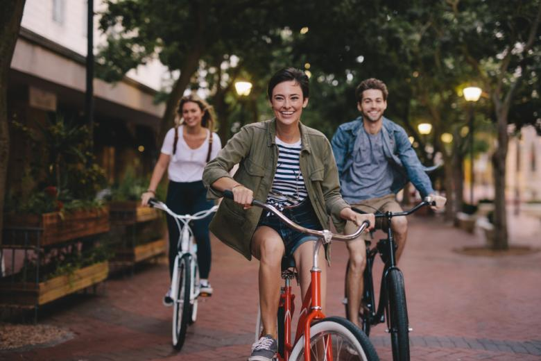 Молодые люди едут по улице на велосипедах фото