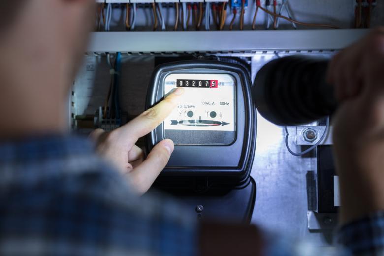 Мужчина снимает показатели счётчика электроэнергии фото