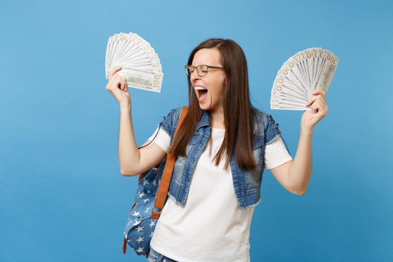 Студентка держит две пачки денег веером фото