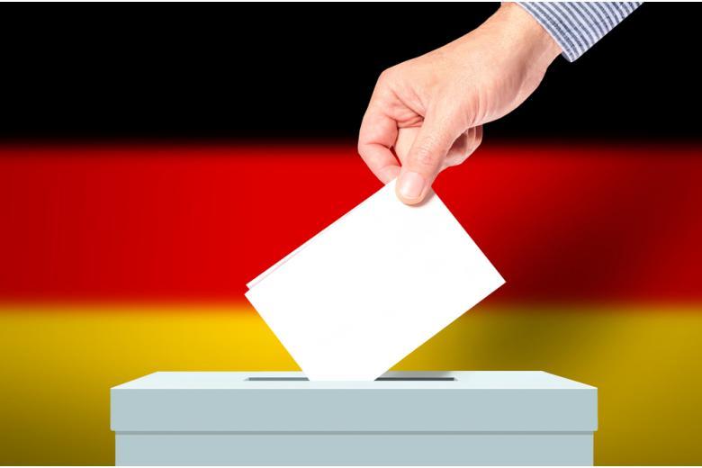 Избиратель опускает бюллетень в урну на фоне флага Германии фото