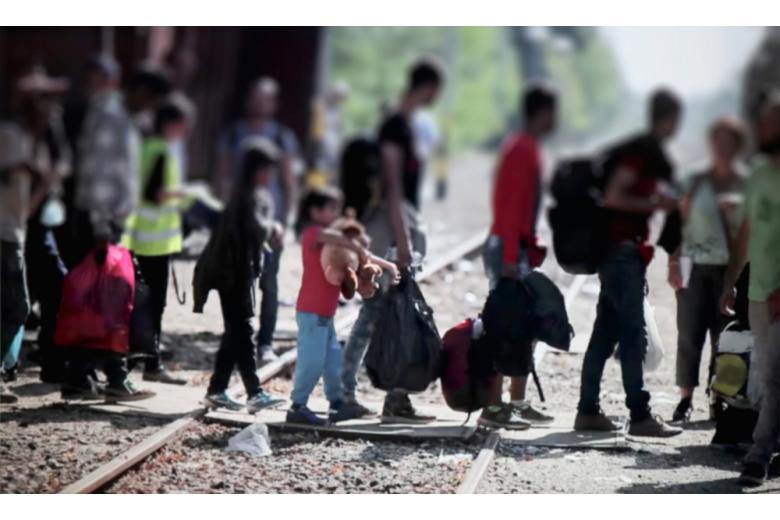беженцы переходят железнодорожный путь размытое фото