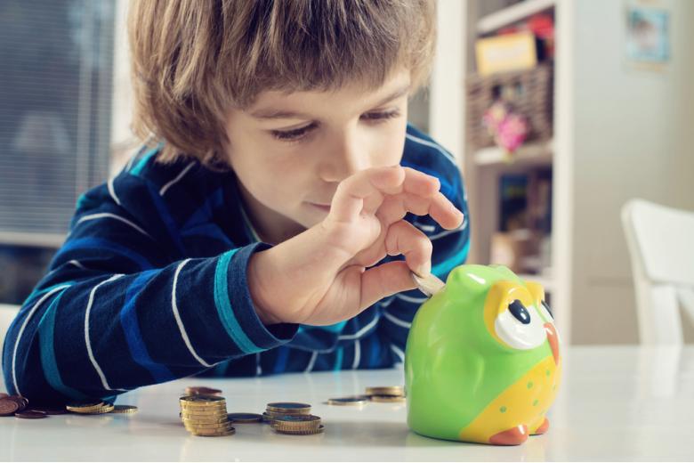 мальчик кладет монеты в копилку-сову фото