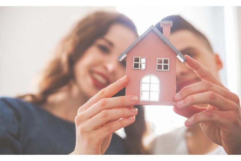 Молодая любящая пара с небольшим деревянным домом фото