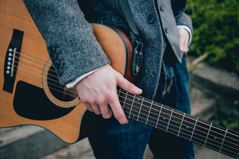 мужчина держит в руках гитару фото