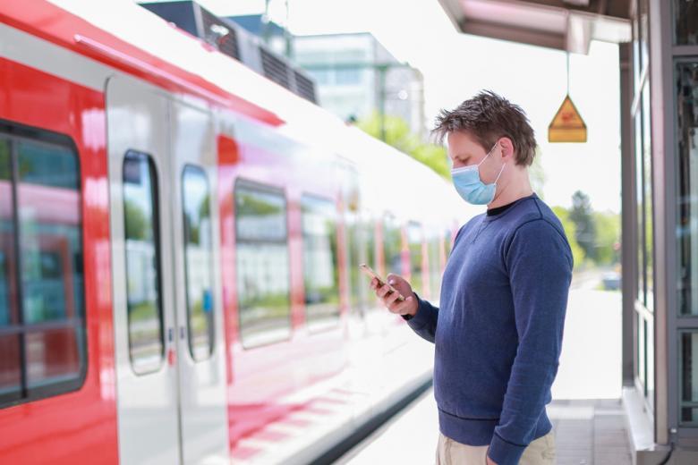 Мужчина в маске на платформе перед поездом Deutsche Bahn фото