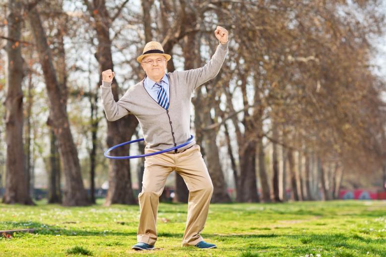 Пенсионер в парке крутит обруч фото