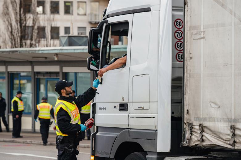 полицейский стоит возле фуры и проверяет документы фото