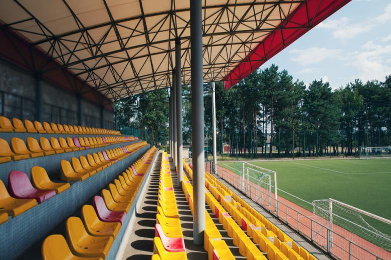 ряды желтых и красных сидений на пустом стадионе фото