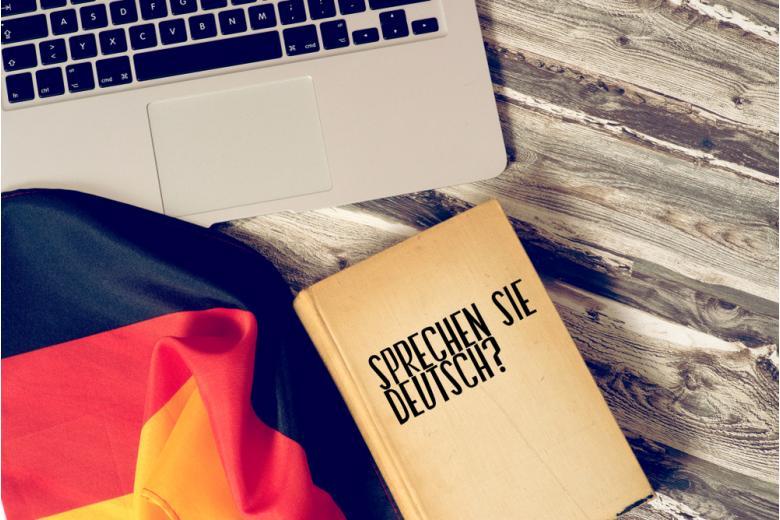 Самоучитель немецкого языка, ноутбук и флаг фото