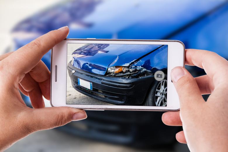 Женщина фотографирует на телефон машину после дтп фото