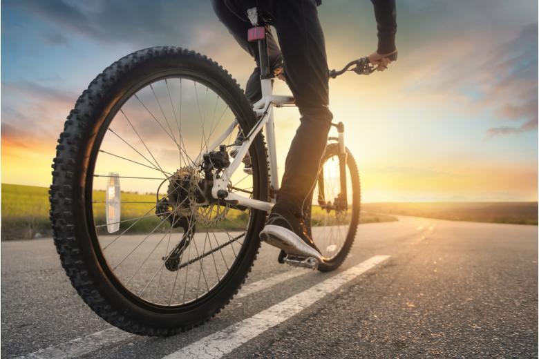 велосипед на дороге колеса и ноги велосипедиста фото