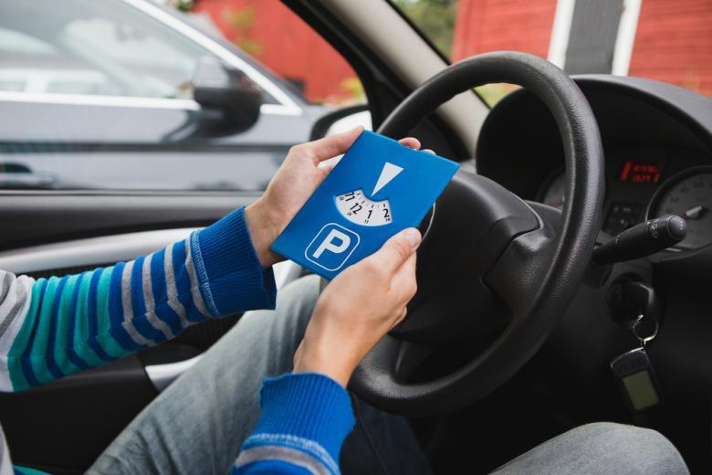 Водитель устанавливает парковочный диск фото