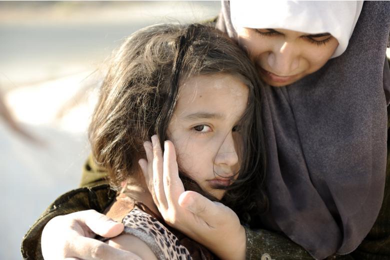 женщина обнимает грустную маленькую девочку фото