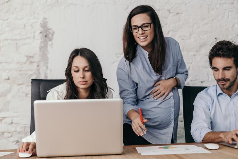 Молодая беременная женщина на работе со своими коллегами фото