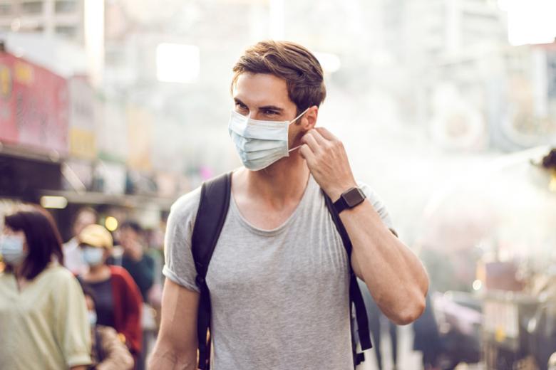 молодой человек снимает маску фото