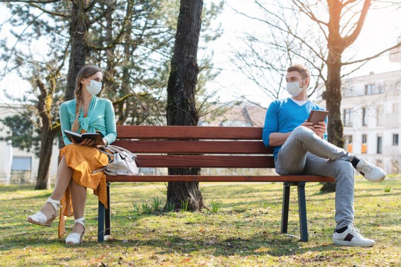 парень и девушка в масках сидят на лавке фото