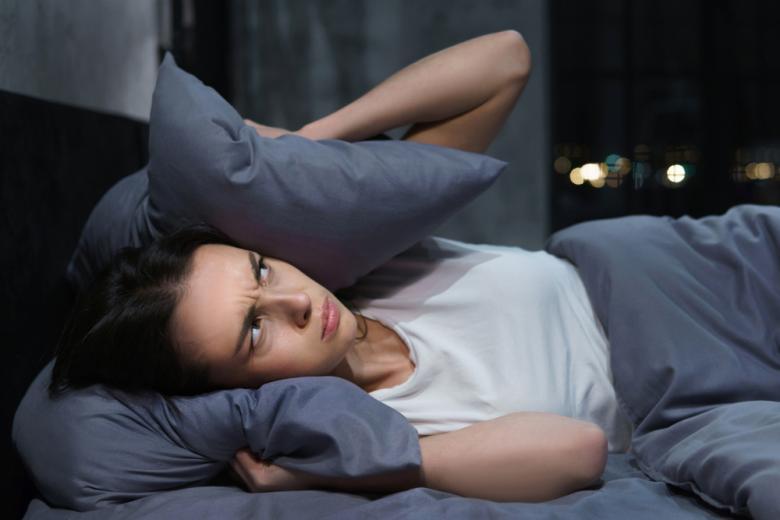раздражённая женщина пытается уснуть фото