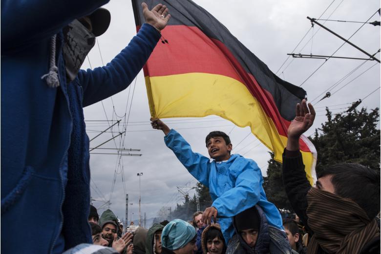 ребенок беженцев машет флагом Германии фото