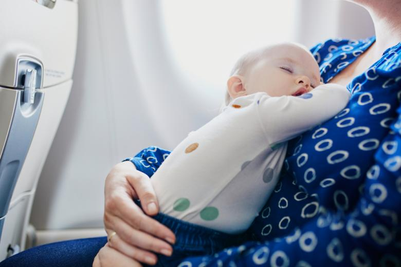 Женщина с младенцем путешествует самолетом фото