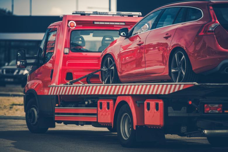 Аварийная служба увозит красный автомобиль фото