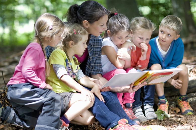 Дети читают на детской площадке фото