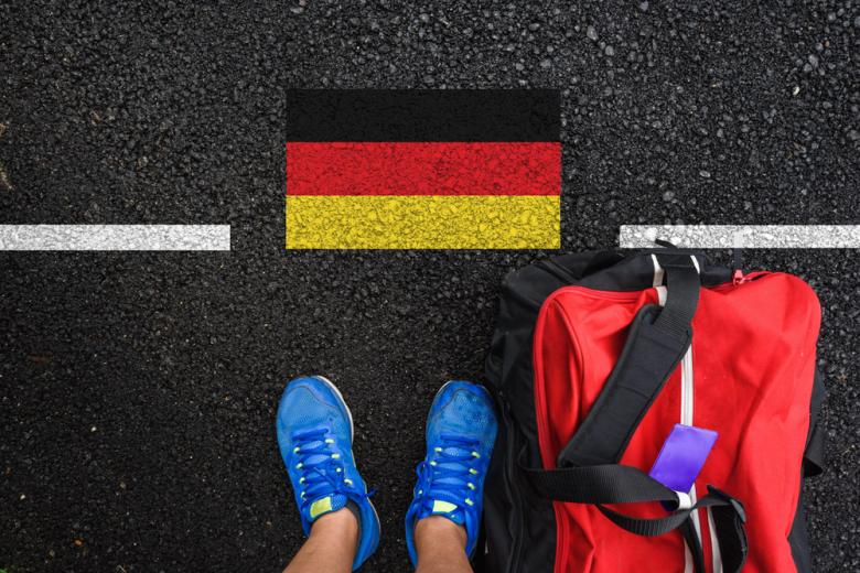 Мужчина с чемоданом у немецкого флага на асфальте фото