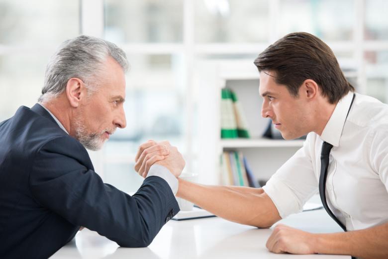 Пожилой и молодой бизнесмен занимаются армрестлингом фото