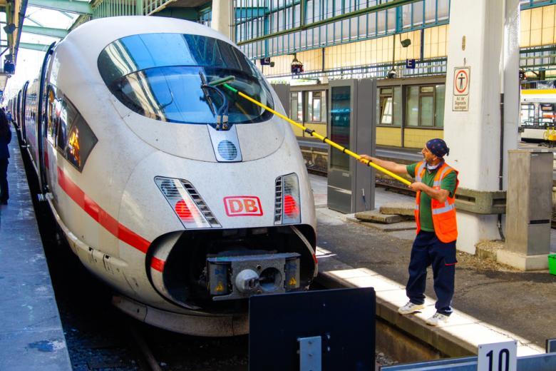 работник Deutsche Bahn моет поезд ICE фото
