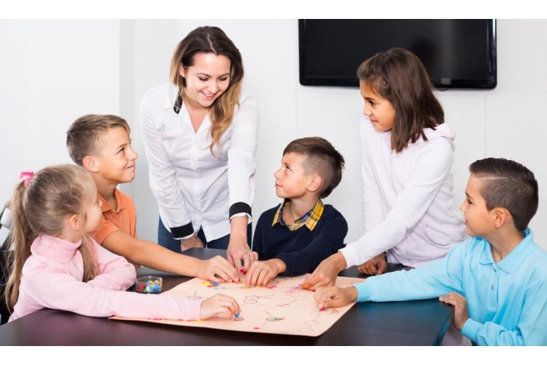 Учитель играет с детьми в настольную игру фото