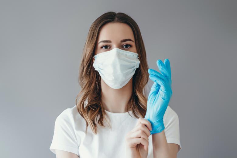 Женщина в медицинской маске одевает перчатку фото
