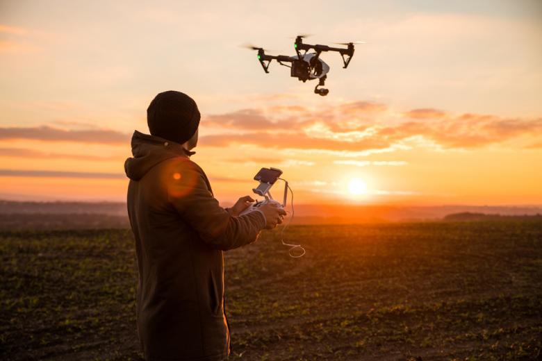 человек управляет дроном на фоне заката фото