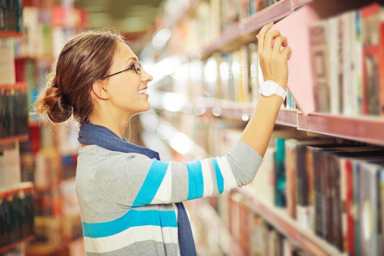 Девушка берущая книгу с полки фото