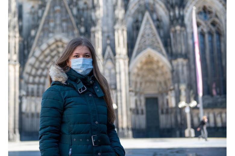 девушка в маске возле собора в Кёльне фото