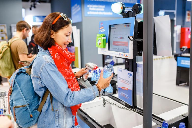 девушка в супермаркете покупает воду через кассу самообслуживания фото