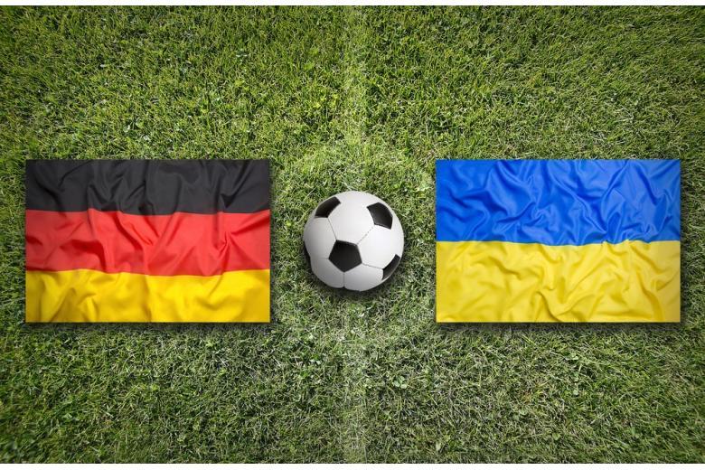 флаги германии и украины, и мяч на футбольном поле фото