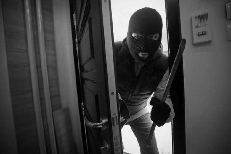 грабитель в маске с ломом в руках у открытой двери фото