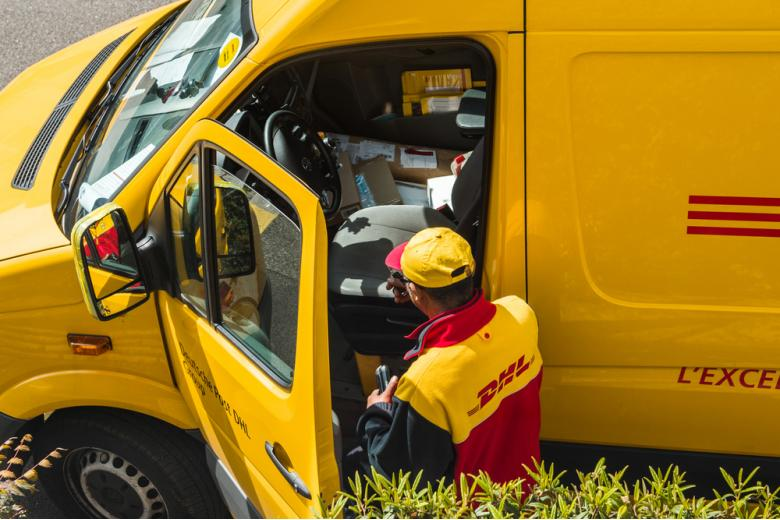 курьер DHL выходит из фургона фото