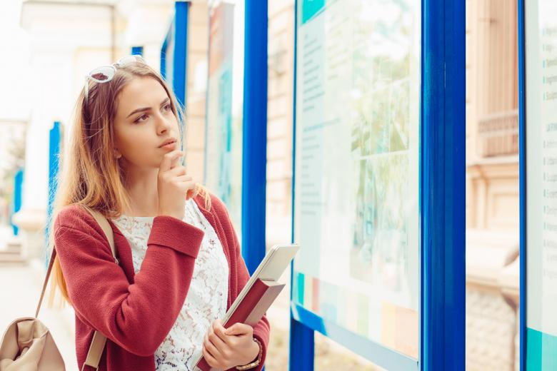 молодая девушка стоит перед стендом в задумчивости