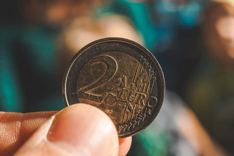монета два евро в пальцах крупным планом фото