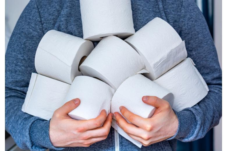 мужчина держит в руках рулоны туалетной бумаги фото