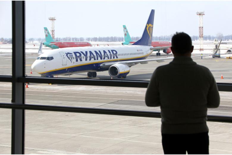 мужчина смотрит сквозь стекло на самолёт фото