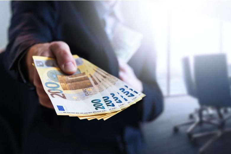 мужчина в костюму держит в руках банкноты евро фото
