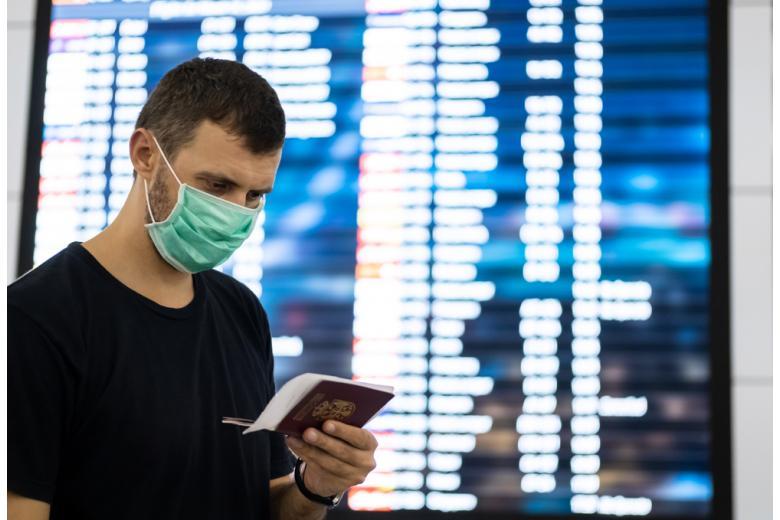 мужчина в маске и с паспортом на фоне табло в аэропорту фото