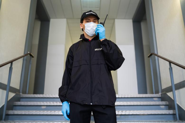 Охранник в маске говорит по рации фото