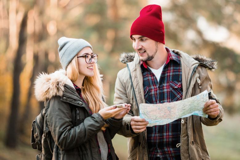 парень и девушка прогуливаются с картой в руках фото