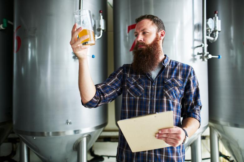 пивовар изучает качество пива в бокале фото