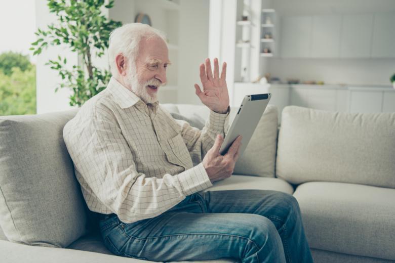 пожилой мужчина с планшетом машет рукой фото