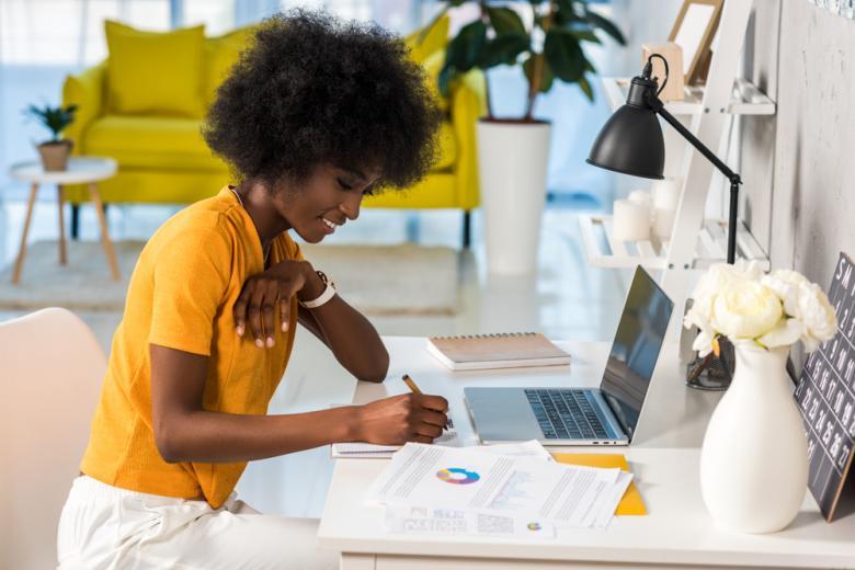 улыбающаяся девушка работает за ноутбуком дома вид сбоку фото